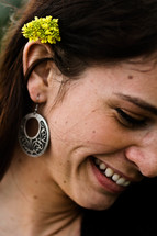 A woman's ear with an earring and flower behind her ear