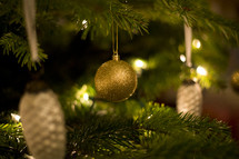 gold Christmas ornaments hanging on a Christmas tree