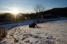 kids sledding down a hill at sunset