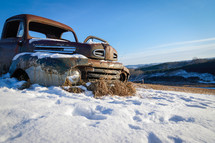 rusted abandoned vehicle in snow