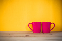 red coffee mugs against a yellow background