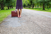 legs of a woman on a rural road next to a suitcase
