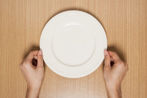 hands holding an empty plate