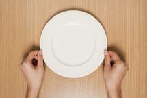 hands holding an empty plate