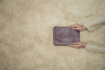 a woman holding a Bible over a rug