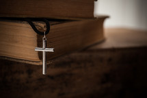 cross necklace and stack of books