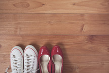 red dress shoes and sneakers on a wooden floor