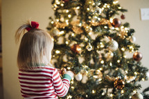 toddler girl in front of a Christmas tree