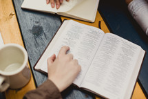 woman reading a Bible and writing in a journal
