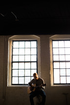 man playing a guitar in front of a window