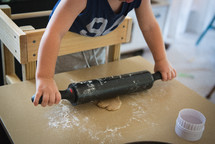 a toddler with a rolling pin and dough