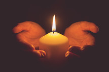 cupped hands holding a burning candle