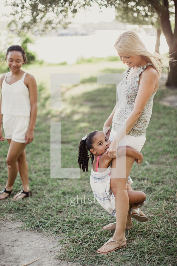 A little girl clings to a woman's legs.