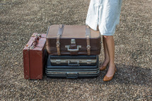 legs of a woman standing next to luggage