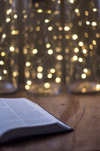 open Bible on a floor in front of bokeh lights from a Christmas tree