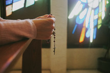 A woman kneeling and praying the rosary in a Catholic church