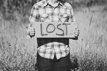 man holding a sign with the words LOST