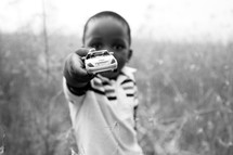 little boy holding out a toy car