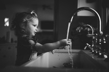 toddler girl washing her hands in a sink