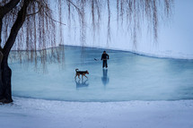 dog and kids playing hockey on a frozen pond