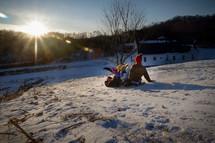 kids sledding down a hill