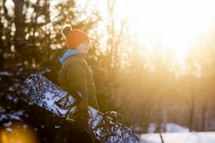 a boy carrying a snowboard