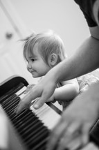 Baby girl learns to play piano with her dad.  Learning to worship.
