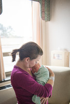 A woman holds a newborn baby in a hospital room.