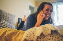 a teen girl talking on a phone in her bedroom