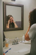 A young woman looking in the mirror unhappy with her self image