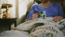 woman under blankets with a coffee mug and book