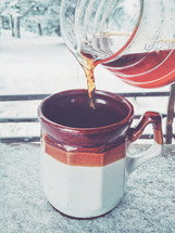 pouring coffee into a mug outdoors in snow