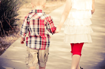 Little brother & big sister holding hands walking