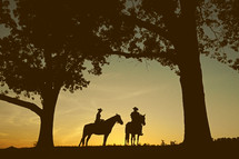silhouettes of cowboys on horses