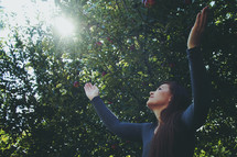 woman standing outdoors with raised hands of worship