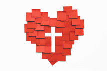 A red heart and a white cross made with squares of paper on a white background.