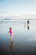 A family walking on wet sand at the beach
