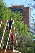 Construction workers putting up roof joists with trees and a tall building in the background.