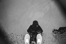 feet and reflection in a puddle