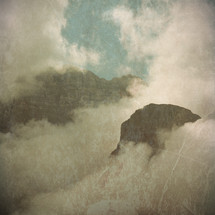tops of mountains engulfed in low clouds - textured for vintage look