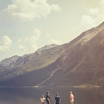 people standing on a mountain lake shore
