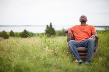 man sitting in a chair in a field relaxing outdoors
