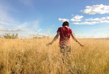 a man walking through a golden field