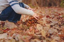 boy child playing in fall leaves