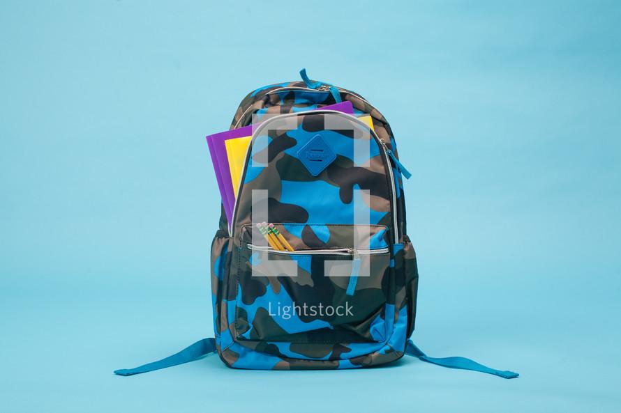Boy's camo backpack on light blue background.