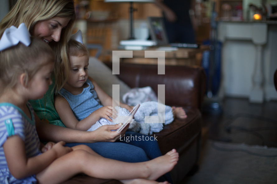 a mother sitting on the couch with her daughters