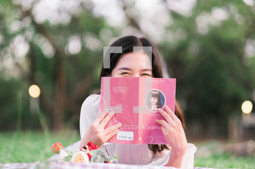 a woman hiding behind the pages of a book