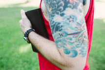 man with a sleeve tattoo holding a Bible