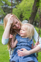 a mother and daughter on a swing