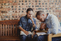 Men praying during a Bible study.